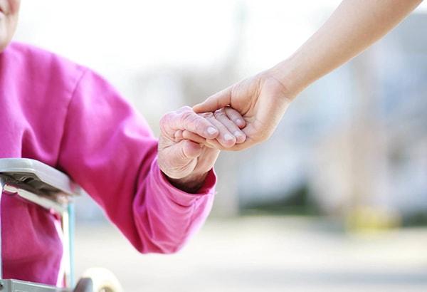 idosa apoiada por pessoa
