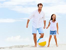 pai e filha a jogar bola na praia