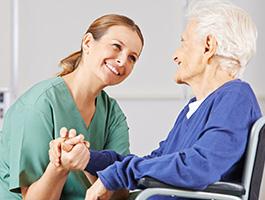 enfermeira a sorrir para idosa