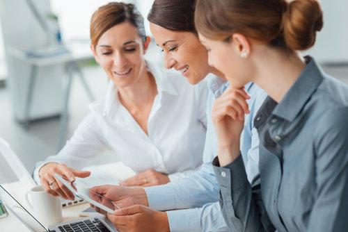 mulheres falam em frente de tablet e pc sobre processo